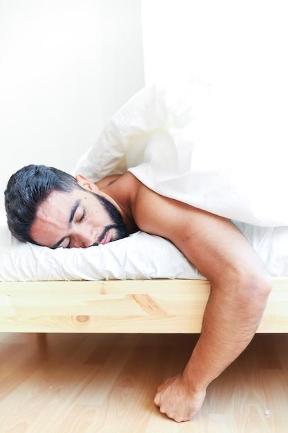 Junger mann, der auf bett schläft Kostenlose Fotos