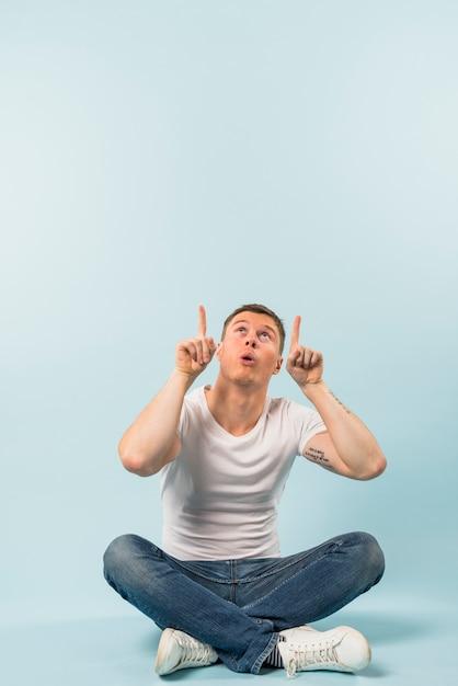 Junger mann, der auf boden mit den gekreuzten beinen sitzt, seine finger aufwärts gegen blauen hintergrund zeigend Kostenlose Fotos