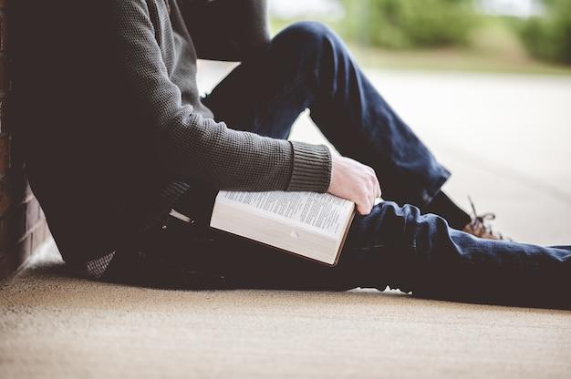 Junger mann, der auf dem boden sitzt und die bibel in seinen händen hält Kostenlose Fotos