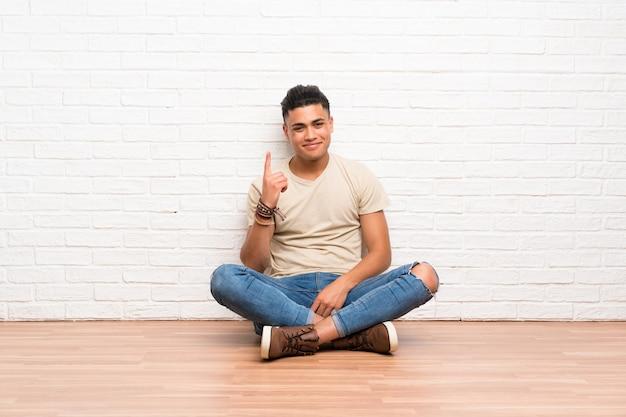 Junger mann, der auf dem boden zeigt mit dem zeigefinger eine großartige idee sitzt Premium Fotos