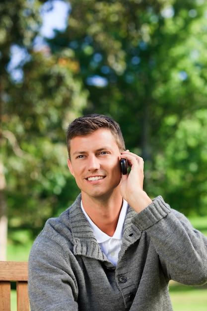 Junger mann, der auf der bank anruft Premium Fotos