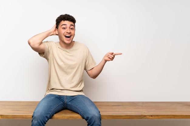 Junger mann, der auf der tabelle überrascht sitzt und finger auf die seite zeigt Premium Fotos