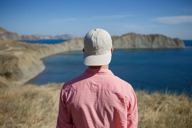 Junger mann, der auf einem gebirgsufer schaut zum meer steht Premium Fotos