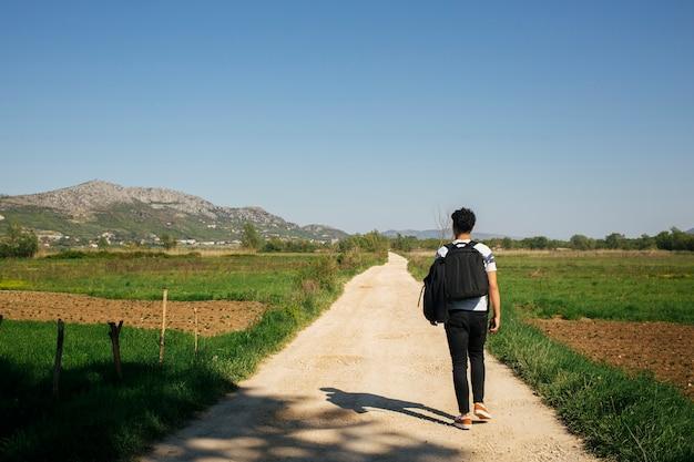 Junger mann, der auf einen naturlehrpfad mit tragendem rucksack geht Kostenlose Fotos