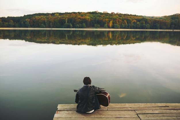 Junger mann, der auf gitarre am see spielt Kostenlose Fotos