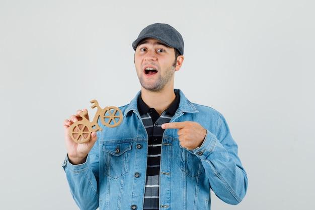Junger mann, der auf hölzernes spielzeugfahrrad in der kappe, im t-shirt, in der jacke zeigt und fröhlich schaut. vorderansicht. Kostenlose Fotos