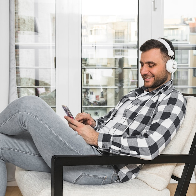 Junger mann, der auf hörender musik des stuhls am kopfhörer durch handy sitzt Kostenlose Fotos