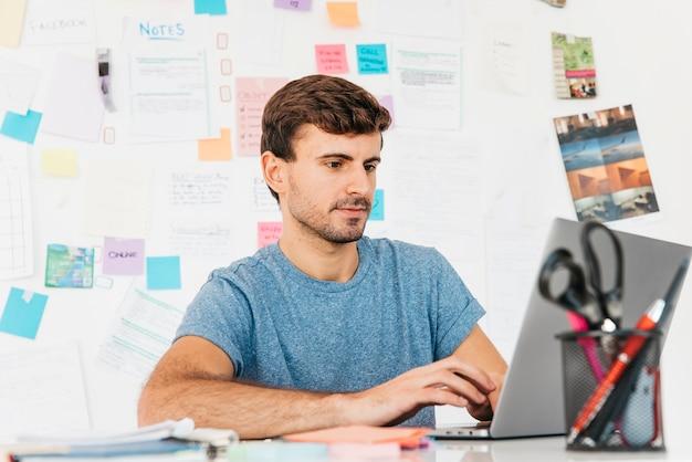 Junger mann, der auf laptop gegen wand mit anmerkungen schreibt Kostenlose Fotos