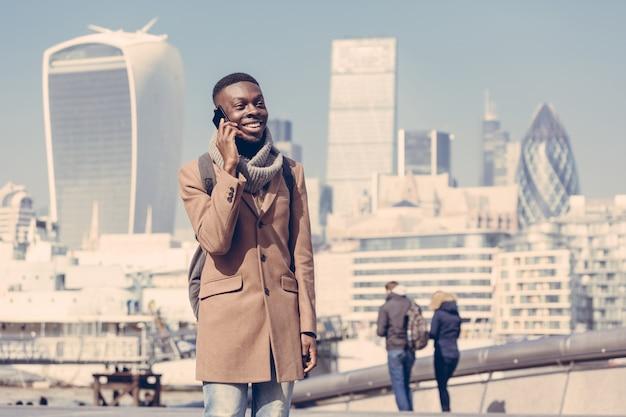 Junger mann, der auf mobile mit london-stadt spricht Premium Fotos