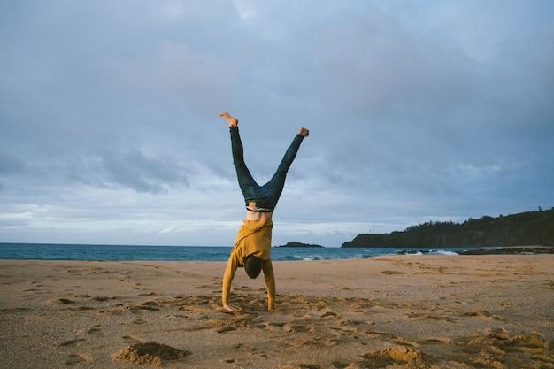 Junger mann, der auf seinen armen am sandstrand an einem sonnigen tag steht Kostenlose Fotos