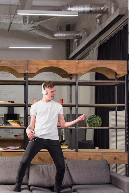 Junger mann, der auf sofa mit kopfhörer auf seinem haupt zu hause tanzt steht Kostenlose Fotos