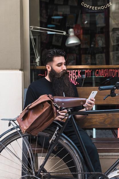 Junger mann, der außerhalb des cafés auf bank mit fahrrad unter verwendung des handys sitzt Kostenlose Fotos