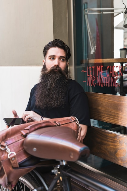 Junger mann, der außerhalb des cafés mit seinem fahrrad sitzt Kostenlose Fotos