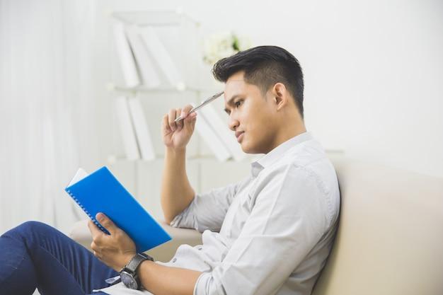 Junger mann, der beim schreiben auf ein buch denkt Premium Fotos