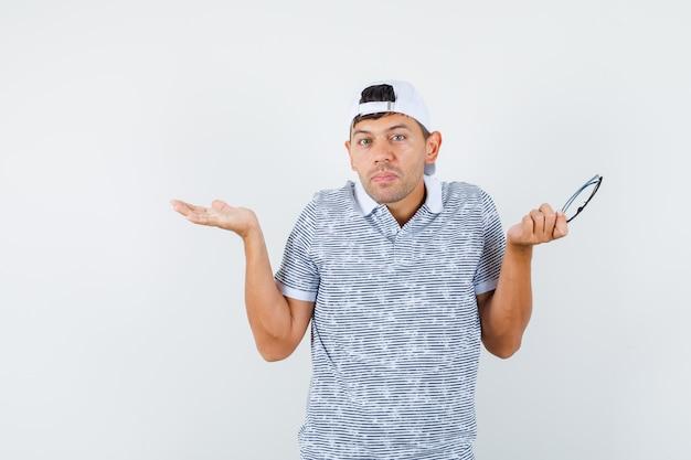 Junger mann, der brille mit hilfloser geste im t-shirt und in der mütze hält und verwirrt schaut Kostenlose Fotos