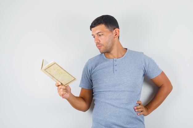 Junger mann, der buch mit hand auf taille im grauen t-shirt liest und vorsichtig schaut. Kostenlose Fotos