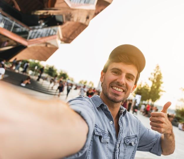 Junger mann, der das lächeln an der kamera gestikuliert Kostenlose Fotos