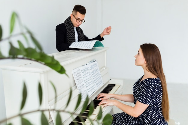 Junger mann, der das musikalische blatt unterstützt die frau spielt klavier unterstützt Kostenlose Fotos