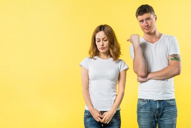 Junger mann, der daumen bis zu ihrer traurigen freundin steht gegen gelben hintergrund zeigt Kostenlose Fotos