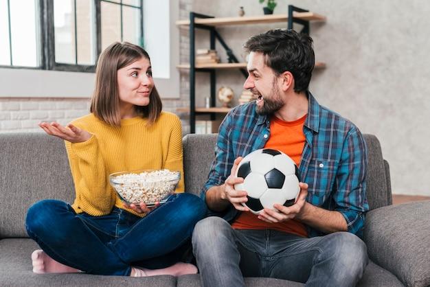 Junger mann, der den fußball in der hand betrachtet ihre freundin hält schüssel popcorns hält hält Kostenlose Fotos