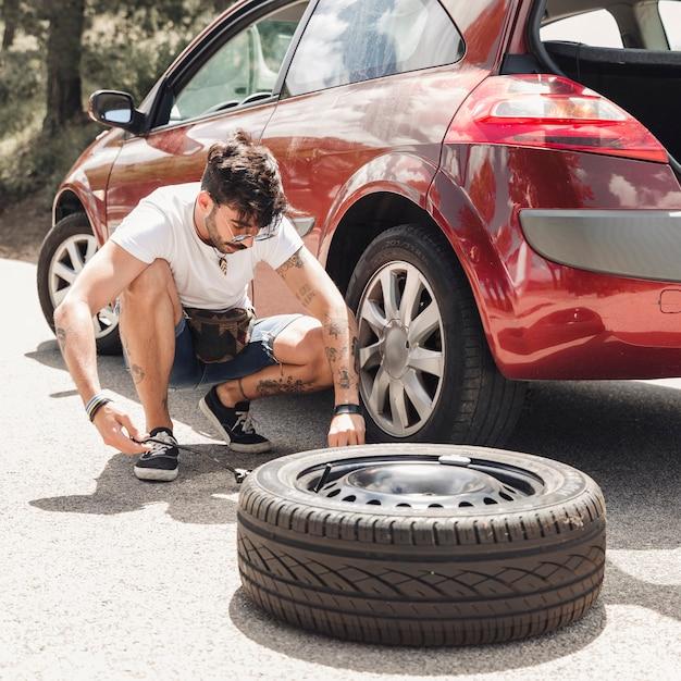 Junger mann, der den reifen des aufgegliederten roten autos ändert Kostenlose Fotos