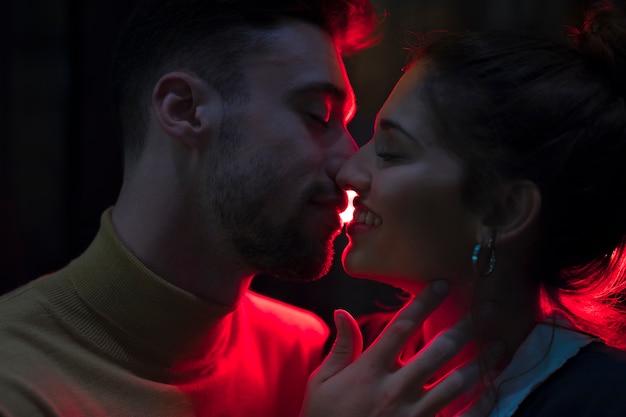 Junger mann, der die lächelnde frau küsst, belichtet durch rote lichter Kostenlose Fotos