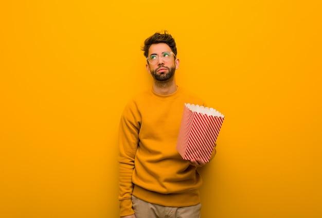 Junger mann, der die popcorn müde und gelangweilt hält Premium Fotos