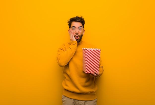 Junger mann, der die popcorn überrascht und entsetzt hält Premium Fotos