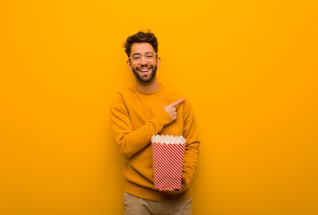 Junger mann, der die popcorn zeigt auf die seite mit dem finger hält Premium Fotos