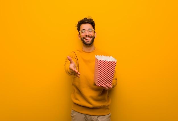 Junger mann, der die popcornholding heraus erreicht, um jemand zu grüßen Premium Fotos