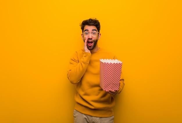 Junger mann, der die popcorns schreien etwas glücklich zur front hält Premium Fotos