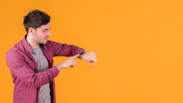 Junger mann, der die zeit auf seiner armbanduhr gegen orange hintergrund überprüft Kostenlose Fotos