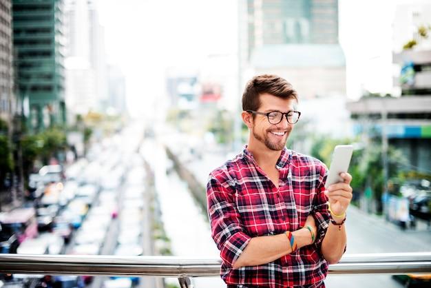 Junger mann, der draußen smartphone-konzept grasen Premium Fotos