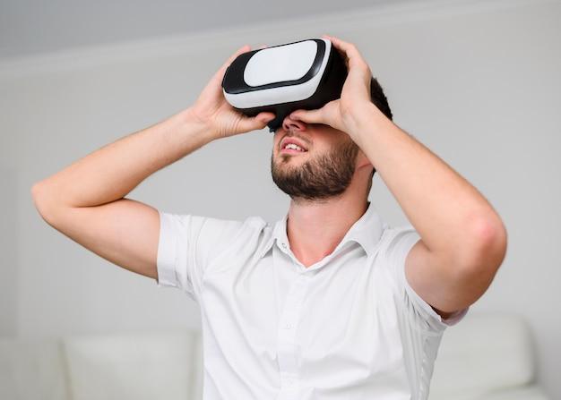 Junger mann, der durch gläser der virtuellen realität schaut Kostenlose Fotos