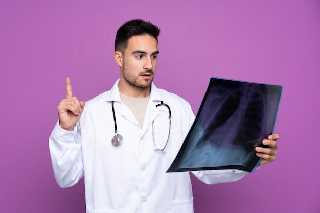 Junger mann, der ein arztkleid trägt und einen knochenscan hält Premium Fotos