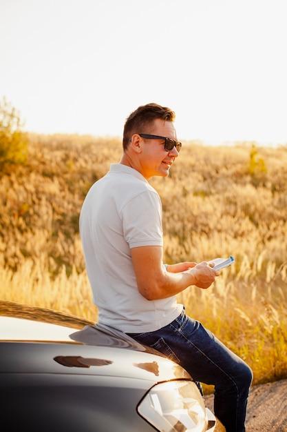 Junger mann, der ein buch auf der autohaube liest Kostenlose Fotos