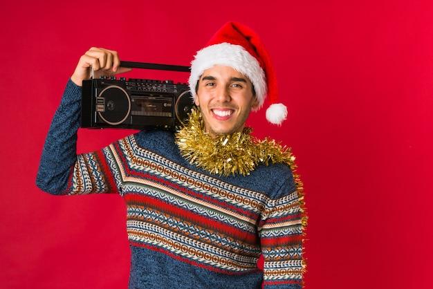 Junger mann, der ein geschenk am weihnachtstag hält Premium Fotos
