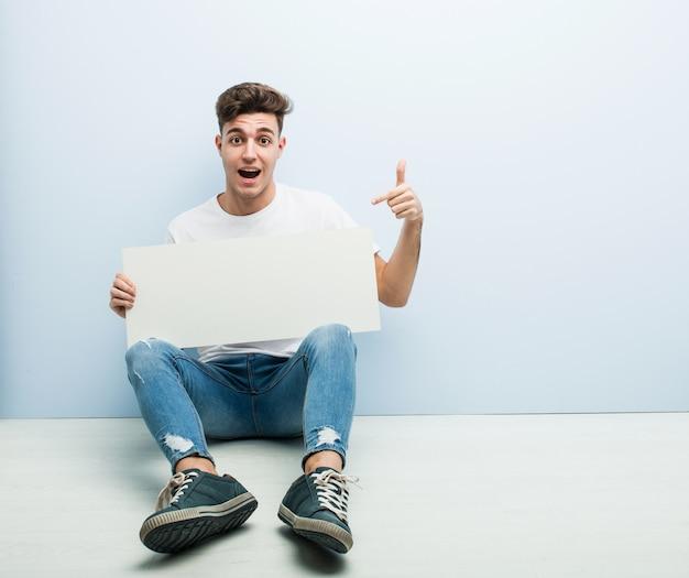 Junger mann, der ein plakat sitzt auf seinem hauptboden lächelt hält, freundlich zeigend mit dem zeigefinger weg. Premium Fotos
