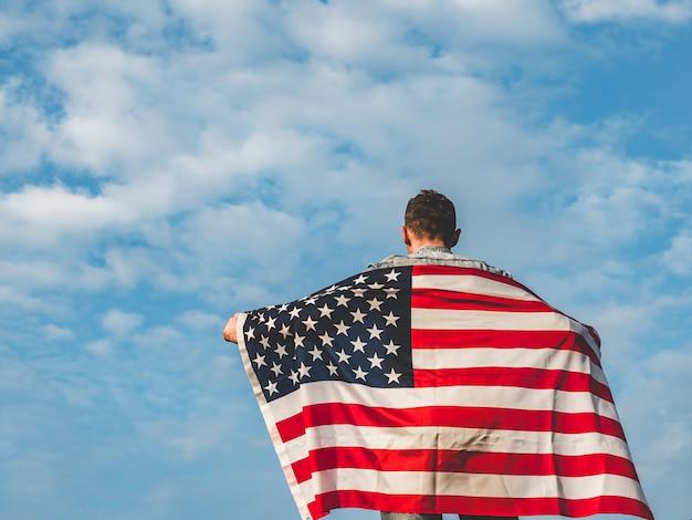 Junger mann, der eine amerikanische flagge wellenartig bewegt Premium Fotos