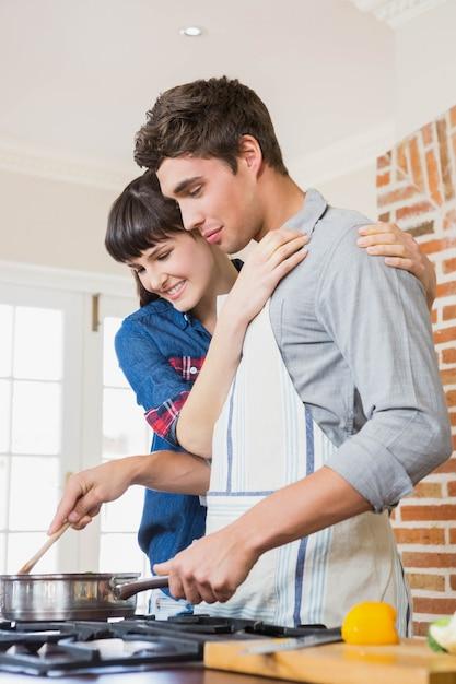 Junger mann, der eine mahlzeit in der küche zubereitet Premium Fotos