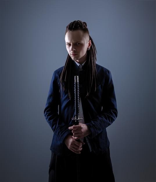 Junger mann, der eine samuraiklinge hält. zauberfoto. Premium Fotos