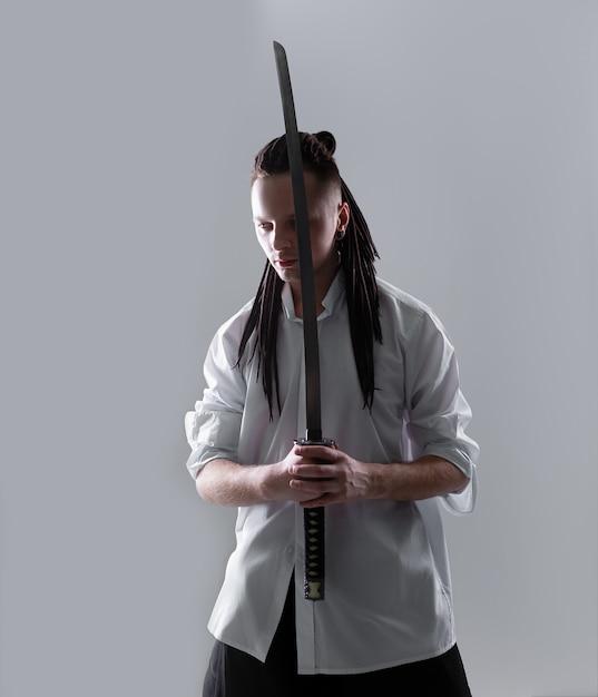Junger mann, der eine samuraiklinge hält. Premium Fotos