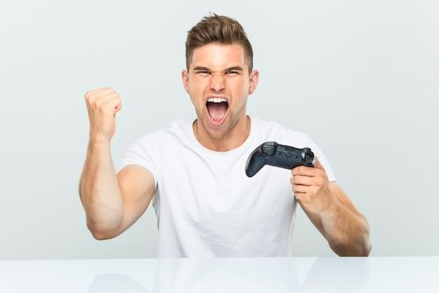 Junger mann, der einen gamecontroller hält, der sorglos und aufgeregt jubelt Premium Fotos