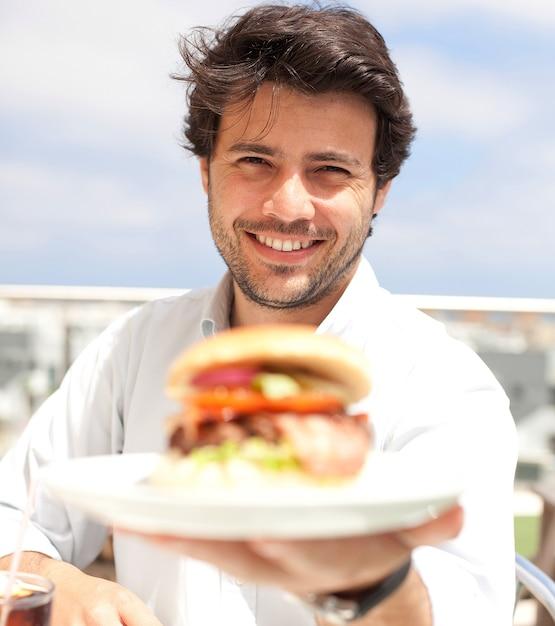 Junger mann, der einen hamburger isst Premium Fotos