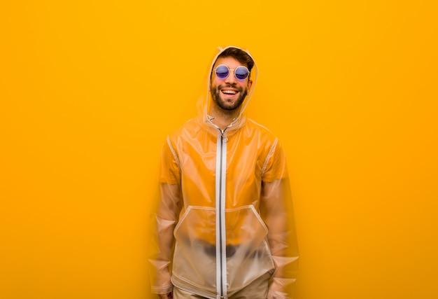 Junger mann, der einen regenmantel freundlich mit einem großen lächeln trägt Premium Fotos