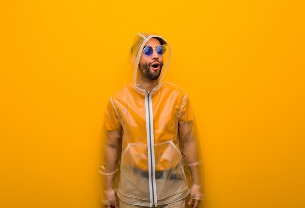 Junger mann, der einen regenmantel träumt vom erreichen von zielen und von zwecken trägt Premium Fotos