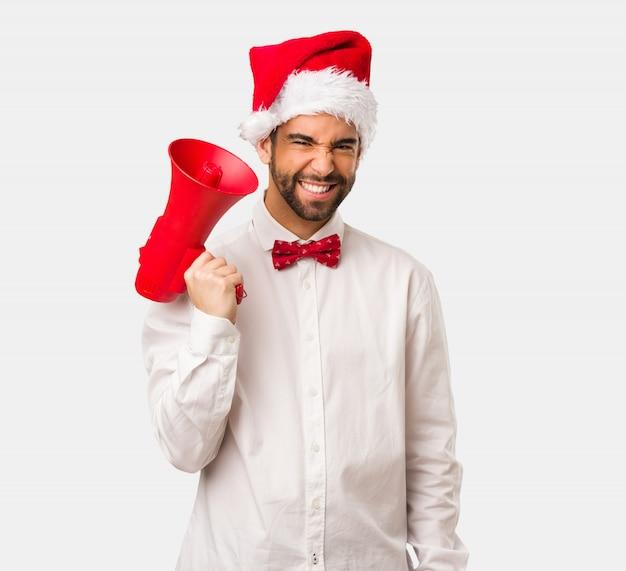 Junger mann, der einen weihnachtsmann-hut am weihnachtstag trägt Premium Fotos