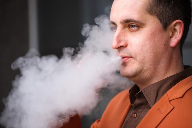 Junger mann, der elektronische zigarette raucht Premium Fotos