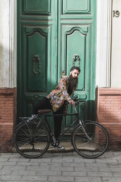 Junger mann, der fahrrad vor großer geschlossener tür fährt Kostenlose Fotos