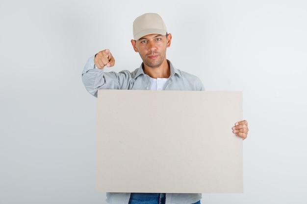 Junger mann, der finger zur kamera mit plakat im hemd mit kappe, jeans zeigt Kostenlose Fotos